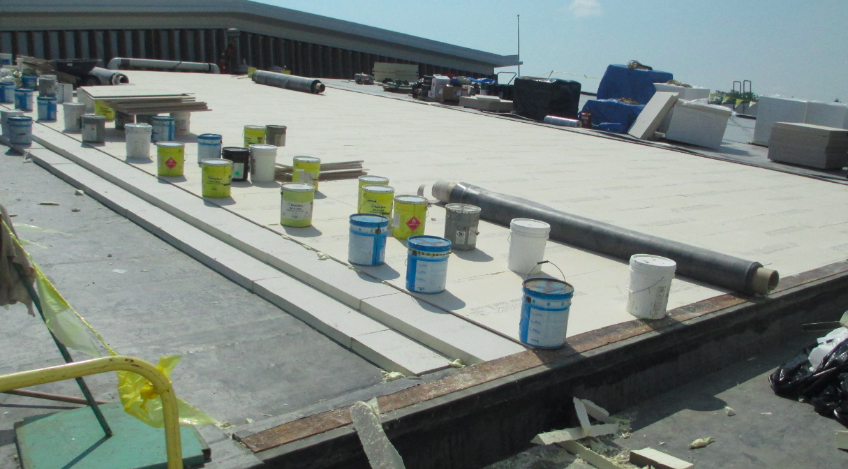 This high-performance roof system was recently installed on a high school north of Chicago. It features two layers of 3-inch 25-psi, double-coated fiberglass-faced polyisocyanurate insulation set in bead-foam adhesive at 4 inches on center, weighted with five 5-gallon pails of adhesive per 4- by 4-foot board to ensure a positive bond into the bead foam until set. PHOTO: Hutchinson Design Group LLC