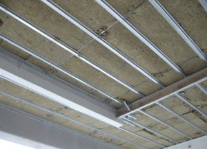 "Drywall ceilings hung on resilient hangers in conjunction with a lightweight roofing system provide even greater sound isolation by virtue of the resilient connection or ""decoupling"" of the drywall layer from the rest of the building structure."