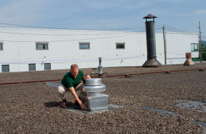 Roof Consultant Mark Sobeck inspects a 35-year-old ballasted EPDM roof on a multi-tenant building in Kingston, Pa.