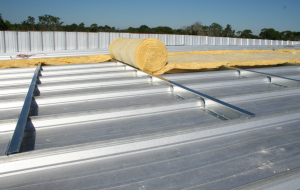 This new standing-seam roof is being installed with 4 inches of additional insulation.