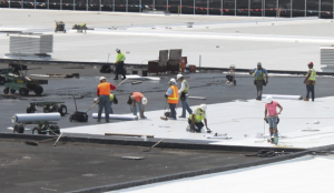 Workers placed 712,000 board feet of 2-inch cellular glass insulation over concrete roof channels, followed by 1,086 rolls of 90-mil membrane in hot asphalt. The fleece-backed membrane with air-welded seams produced an integrated roof system backed by a 30-year warranty.