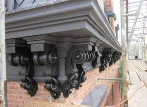 The cornice ornamentation and decoration beneath the built-in gutters is no small feat to replicate.
