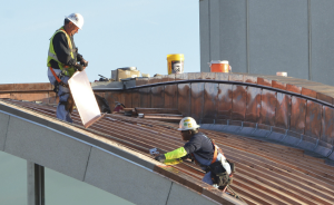 Workers install CopperPlus batten-seam panels over a dome at Lambert-St. Louis International Airport. Stepby- step, the installation of CopperPlus is virtually identical to that of copper.