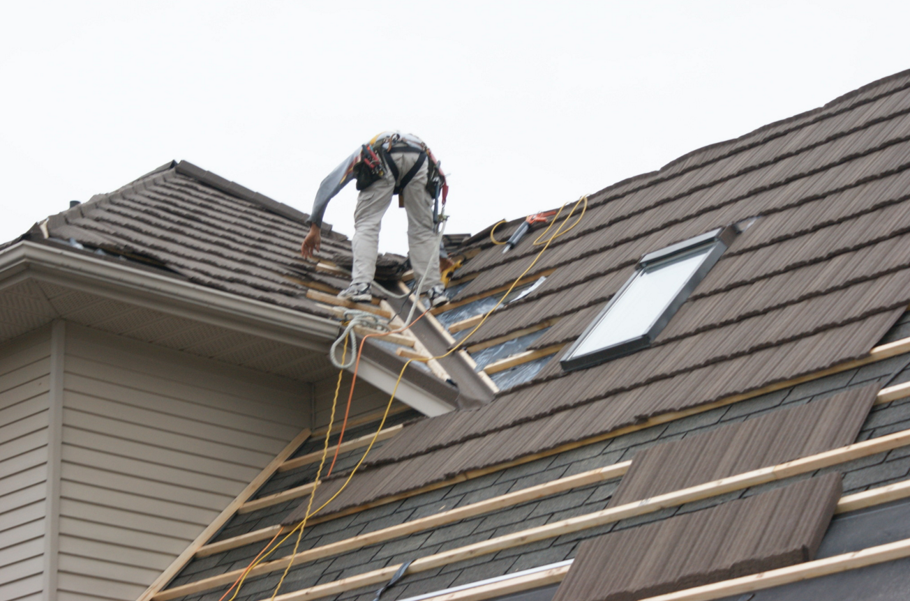An installation team from Metal Roof Outlet, Courtland, Ontario, Canada, installs an Allmet stone-coated metal roof on a suburban Toronto home.