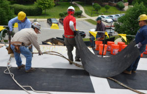 Asphaltic core boards are very flexible and will conform to irregular surfaces and offsets without fracture. Here crews work to install the cover board in bead-foam adhesive in preparation for the three-ply modified bitumen roof cover. PHOTO: Clark Roofing