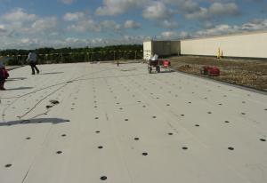 High-density polyisocyanurate is gaining fans with its light weight and ease of handling. In this photo, it is being mechanically fastened in a RhinoBond application. PHOTO: Clark Roofing