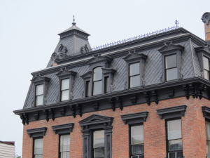 The mansard roof is the character-defining feature of the Second Empire style. A mansard is essentially a hipped gambrel. The lower roof, between the eaves and upper cornice, is most often covered in slate.
