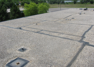 PHOTO 1: This EPDM roof's service has been extended for nine years and counting, approaching 30 years in-situ performance. Here, the restoration of perimeter gravel- stop flashing and lap seams, as well as detailing of roof drains, penetrations and roof curbs, is nearing completion.