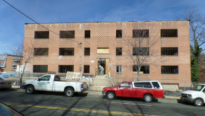 three low-rise apartment buildings at the intersection of Southern Avenue and Benning Road in Washington, D.C., stood derelict and abandoned, uninhabitable reminders of 1960s brick and block construction.