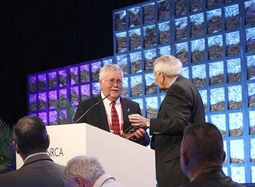 John Gooding accepts the 2016 J.A. Piper Award from 2015 J.A. Piper Award Winner Don McCrory during NRCA's 129th Annual Convention.