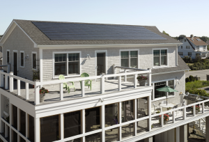 The Westerly, R.I., coastal home features an asphalt laminate shingle and integrated solar shingle roofing system.