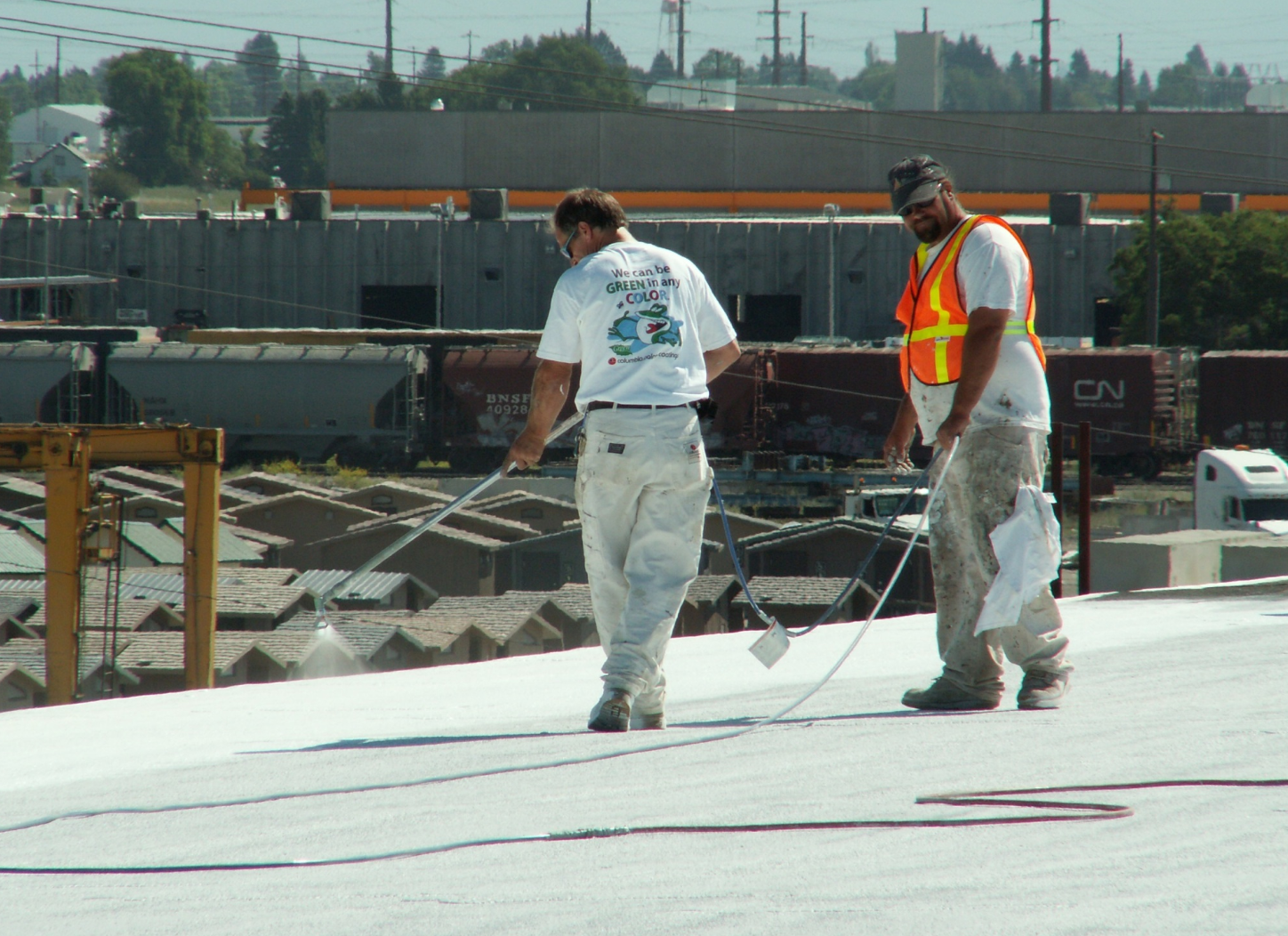 A spray-applied reflective coating is being installed over an existing granule-surfaced asphaltic roof. PHOTO: GAF, courtesy of the Roof Coatings Manufacturers Association