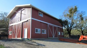 To achieve the traditional barn aesthetic, the wall panels are coated in a Rustic Red color of Fluropon while the metal roof panels are finished in Polar White.