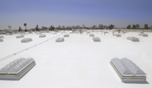 American International Industries restored sections of its roof with a cold-applied system, spray polyurethane expanding foam and smoke-vent skylights. Photo courtesy of SKYCO Skylights.